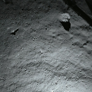 This image was taken by the Philae comet lander looking down using its descent ROLIS imager when it was about 130 feet (40 meters) above the surface of Comet 67P/Churyumov-Gerasimenko.   It shows that the surface of the comet is covered by dust and debris ranging from mm to metre sizes. The large block in the top right corner is 5 meters in size. In the same corner the structure of the Philae landing gear is visible.   The aim of the ROLIS experiment is to study the texture and microstructure of the comet's surface. ROLIS (ROsetta Lander Imaging System) has been developed by the DLR Institute of Planetary Research, Berlin.   Credit: ESA/Rosetta/Philae/ROLIS/DLR