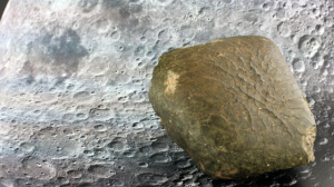 The lunar meteorite Oued Awlitis 001 with the surface of the Moon as background. Credit: L. Ferrière
