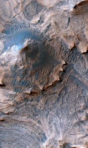 Enhanced color image of a hill in the Candor Colles region of Candor Chasma, Mars. Image is 1 km (0.62 miles) across.  Credit: USGS/NASA/JPL/University of Arizona