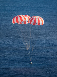 NASA's Orion spacecraft is lowered gently to the Pacific Ocean under its three massive main parachutes at 11:29 am EST on Dec. 5, 2014. Orion launched on its first test flight at 7:05 am and over the course of two orbits and 4.5 hours, traveled 3,600 miles above Earth to test systems critical to human deep space exploration.  Photo credit: NASA/James Blair