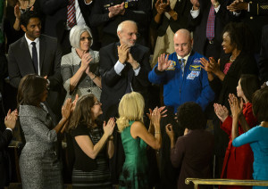 NASA astronaut Scott Kelly stands as he is recognized by President Barack Obama, while First lady Michelle Obama, front left, and other guest applaud, during the State of the Union address on Capitol Hill in Washington, Tuesday Jan. 20, 2015. This March, Astronaut Scott Kelly will launch to the International Space Station and become the first American to live and work aboard the orbiting laboratory for a year-long mission. While living on the International Space Station, Kelly and the rest of the crew will carry out hundreds of research experiments and work on cutting-edge technology development that will inspire students here at home in science, technology, engineering and math.  Photo Credit: NASA/Bill Ingalls