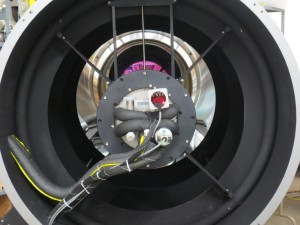 A view down the throat of the DFM telescope with the ATLAS camera mounted on the spider ring. The magenta area is the reflection off of the interference visual filter in front of the ATLAS detector and the primary mirror. Credit: ATLAS Project