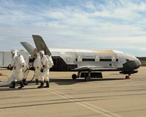 Recovery crew members process the X-37B Orbital Test Vehicle at Vandenberg Air Force Base last year after completing 674 days in space. A total of three X-37B missions have been completed, totaling 1,367 days on orbit. Credit: Boeing