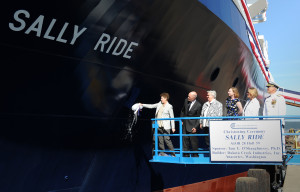 Tam O'Shaughnessy, ship's sponsor for the auxiliary general oceanographic research (AGOR) vessel R/V Sally Ride (AGOR 28), breaks a bottle across the bow during a christening ceremony in August 2014 at the Dakota Creek Industries, Inc., shipyard in Anacortes, Washington.  Joining O'Shaughnessy on the platform are Dick Nelson, president, Dakota Creek Industries, Inc., Matron of Honor, the reverend Dr. Bear Ride, Matron of Honor, Kathleen Ritzman, assistant director, Scripps Institution of Oceanography, University of California San Diego, Kathryn Sullivan, undersecretary of commerce for oceans and atmosphere and administrator, National Oceanic and Atmospheric Administration, and Rear Adm. Matthew Klunder, chief of naval research.  Credit: U.S. Navy photo by John F. Williams