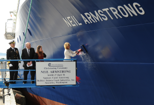 Carol Armstrong, ship sponsor for the Auxiliary General Oceanographic Research (AGOR) research vessel (R/V) Neil Armstrong (AGOR 27), breaks a bottle across ship's bow during a March 2014 christening ceremony at Dakota Creek Industries, Inc. shipyard in Anacortes, Washington. Joining Armstrong on the platform are Rear Adm. Matthew Klunder, left, chief of naval research, Mr. Dick Nelson, president, Dakota Creek Industries, Inc., and Kali Armstrong, granddaughter of the late astronaut.  Credit: U.S. Navy photo by John F. Williams